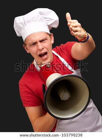 portrait of a young cook man screaming with a megaphone and gesturing over a black background