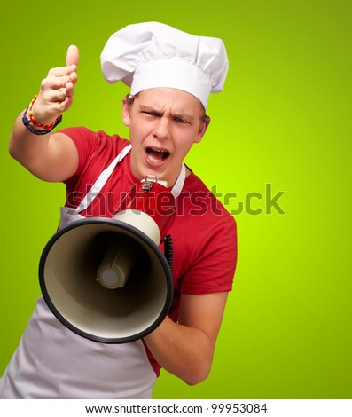 portrait of a young cook man screaming with a megaphone and gesturing over a green background - stock photo
