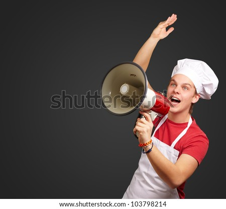 portrait of a young cook man shouting with a megaphone over a black background - stock photo