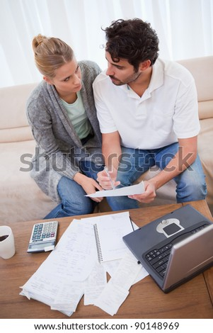 Portrait of a young couple doing their accounting with a notebook in their living room - stock photo