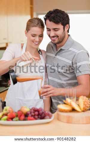 Portrait of a young couple drinking fruits juice in their kitchen