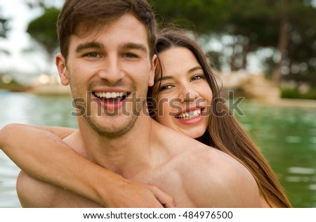 Portrait of a young couple embraced inside the pool