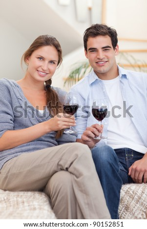 Portrait of a young couple having a glass of red wine in their living room - stock photo