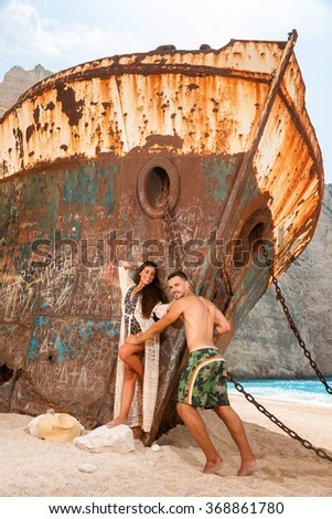 portrait of a young couple in a beach with an old shipwreck