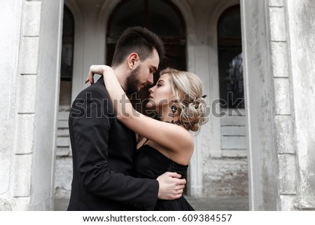 Portrait of a young couple in black suit and dress. Wedding photo.