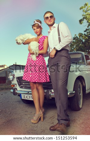 Portrait of a young couple in front of car - stock photo