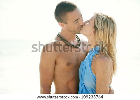 Portrait of a young couple kissing while on the beach on vacation. - stock photo