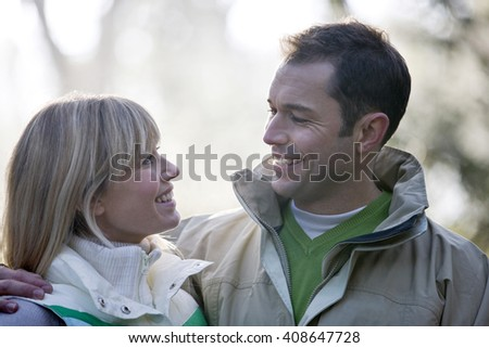 Portrait of a young couple looking at each other, smiling - stock photo
