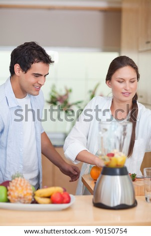 Portrait of a young couple making fresh fruits juice in their kitchen - stock photo