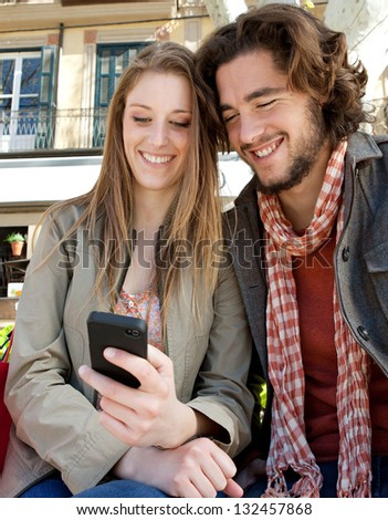 Portrait of a young couple on vacation in a destination city, sitting down with shopping bags and using a smartphone device during a sunny day. - stock photo