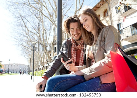 Portrait of a young couple on vacation in a destination city, sitting down with shopping bags to take a break and using a smart phone device during a sunny day. - stock photo
