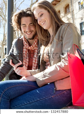 Portrait of a young couple on vacation in a destination city, sitting down with shopping bags to take a break and using a smartphone device during a sunny day. - stock photo