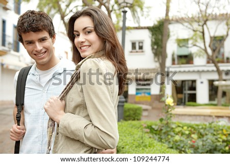 Portrait of a young couple on vacations in a picturesque town square.