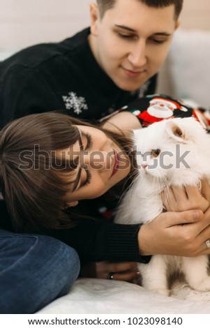 Portrait of a young couple posing with white cat in a cosy room