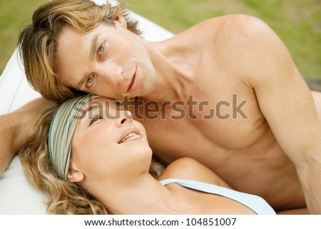 Portrait of a young couple relaxing on a sun bed, outdoors.