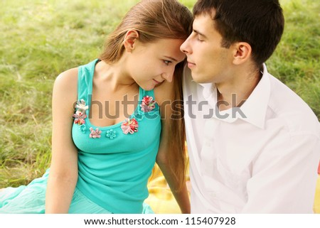 Portrait of a young couple sitting hugging each other - stock photo
