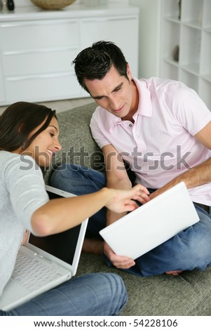 Portrait of a young couple  sitting on a sofa with laptop computers