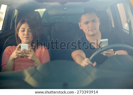 Portrait of a young couple texting and driving together, as seen through the windshield - stock photo