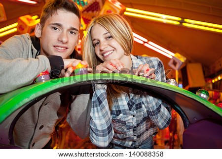 Portrait of a young couple visiting a funfair at night with colorful lights and rides in the background, smiling at camera and having fun. - stock photo