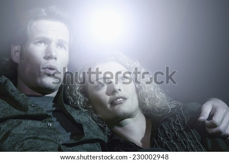 Portrait of a young couple watching a movie - stock photo