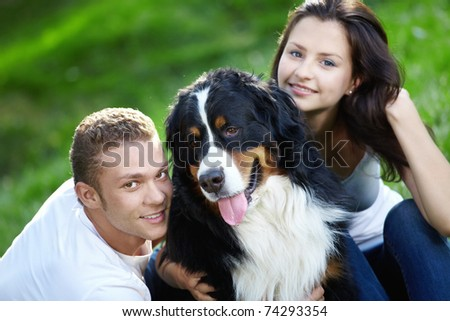 Portrait of a young couple with a dog - stock photo
