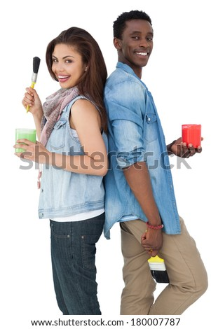 Portrait of a young couple with paintbrushes and containers over white background