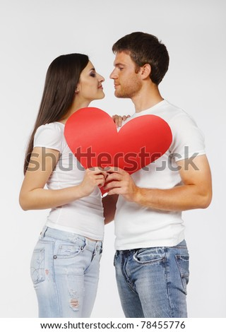 Portrait of a young couple with red heart - stock photo