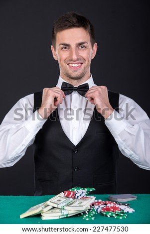 Portrait of a young croupier with gambling chips on the green table. - stock photo