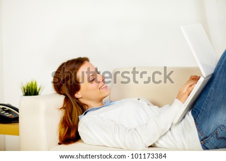 Portrait of a young cute woman lying on sofa and working on laptop - stock photo