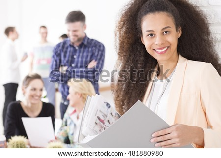 Portrait of a young dark-skinned woman in a modern office, holding a portfolio with photos