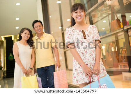 Portrait of a young daughter standing and smiling in the shopping mall on the foreground