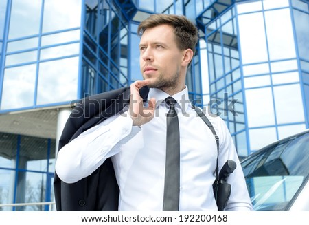 Portrait of a young detective with a gun on a background of the business center