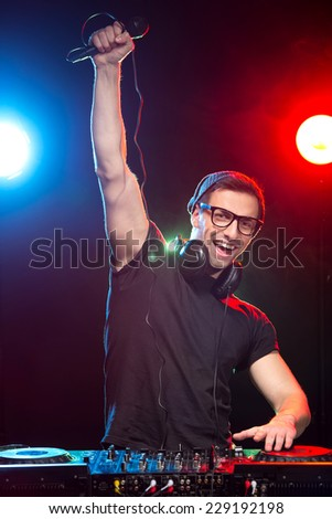 Portrait of a young DJ at work with a microphone and the club lights on the background. - stock photo