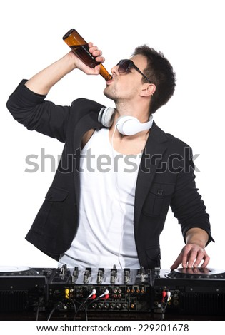 Portrait of a young DJ standing at the mixer and drinking beer on a light background. - stock photo