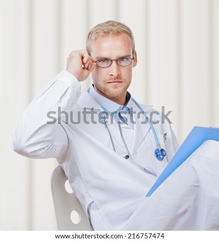 Portrait of a Young Doctor with Stethoscope and Glasses Looking - stock photo