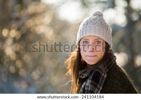 Portrait of a young Dutch woman in winter woods, while wearing a woolen cap and with beautiful bokeh and rimlight in woods near Breda, the Netherlands - stock photo