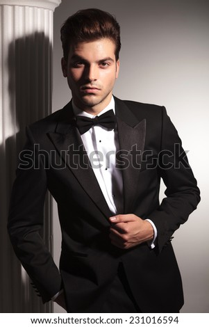 Portrait of a young elegant business man fixing his jacket while looking at the camera. - stock photo