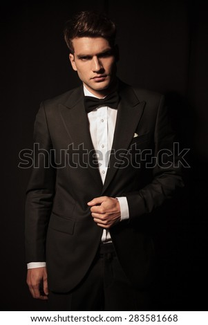 Portrait of a young elegant business man posing on black studio background.