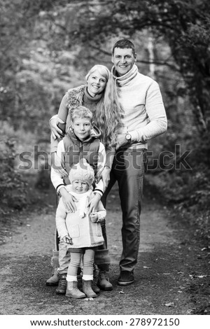 Portrait of a young family in the autumn park
