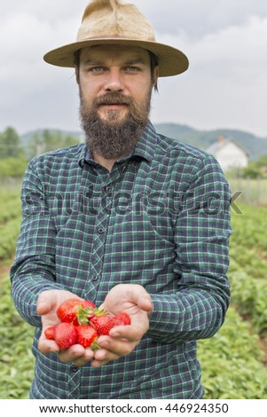 Portrait of a young farmer outside on the field presenting his harvest,red fresh picked strawberries - stock photo