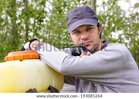 Portrait of a young farmer resting  in his orchard  - stock photo