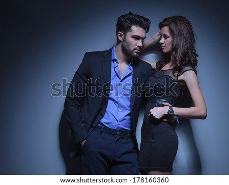 portrait of a young fashion man holding a beautiful woman while looking away with his hand in his pocket. on a dark blue background - stock photo