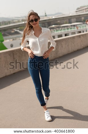 Portrait of a young fashionable brunette woman having fun outdoors in the city.