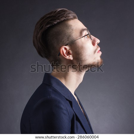portrait of a young fashionable hipster man in profile - stock photo