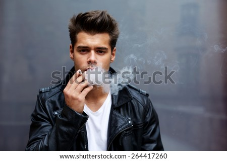 Portrait of a young fashionable man smoking a cigarette with copy space looking to the camera, confident man exhaling cigarette smoke or blowing smoke out of his mouth standing on grey background - stock photo