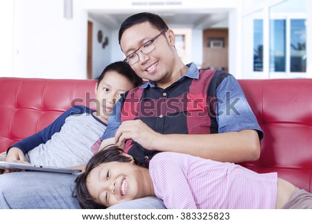 Portrait of a young father sitting on the sofa while spoiling his children at home