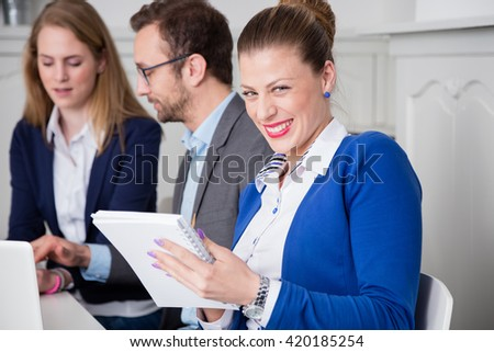 Portrait of a young female business professional at the table during the meeting  - stock photo