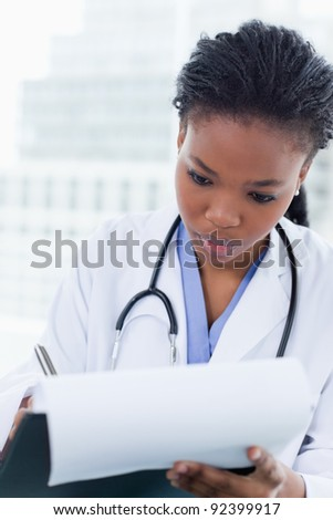 Portrait of a young female doctor signing a document in her office