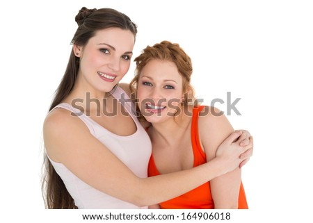 Portrait of a young female embracing her friend over white background