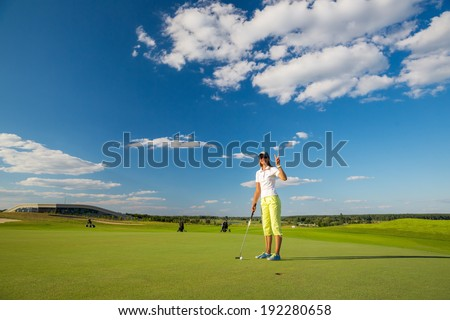 portrait of a young female golf player playing on green